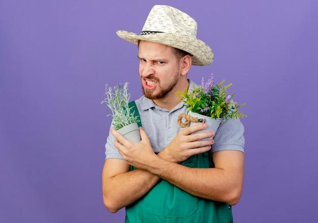 コピースペースと紫色の壁に隔離された植木鉢を保持している手を交差させたままの制服と帽子の怒っている若いハンサムなスラブ庭師
