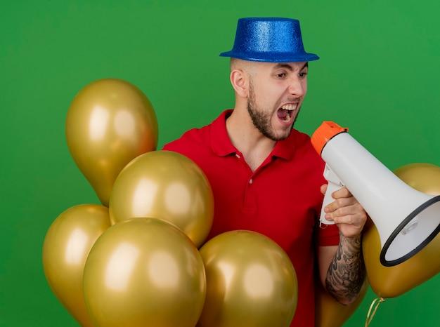 緑の背景に分離されたラウドスピーカーで叫んでいる側を見て風船の間に立っているパーティーハットを身に着けている怒っている若いハンサムなスラブ党の男