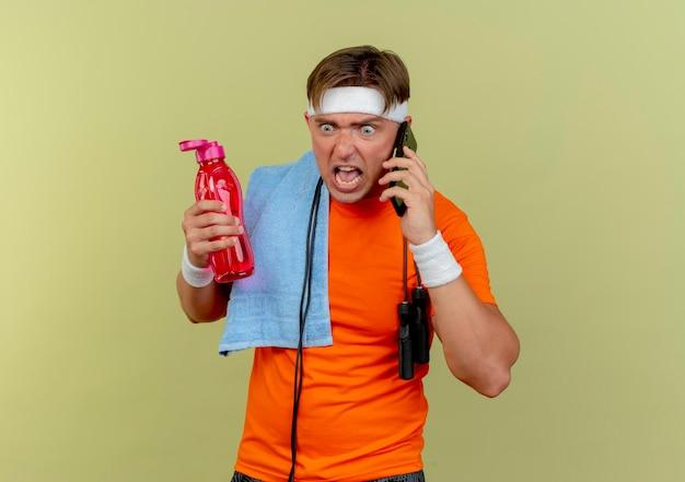 Сердитый молодой красивый спортивный мужчина в головной повязке и браслетах со скакалкой на шее и полотенцем на плече держит бутылку с водой и разговаривает по телефону