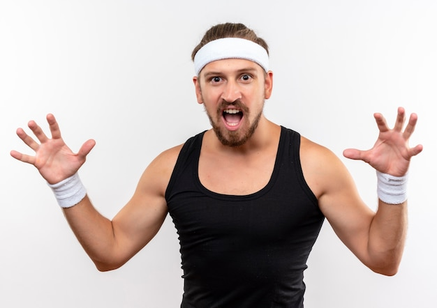 Angry young handsome sporty man wearing headband and wristbands doing tiger roar gesture isolated on white wall