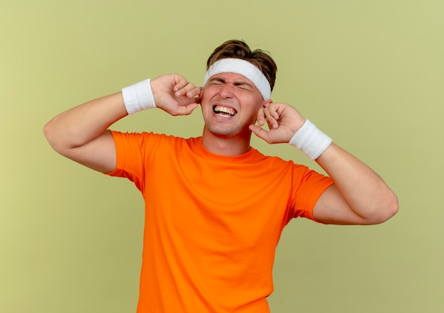 Angry young handsome sporty man wearing headband and wristbands putting fingers in ears with closed eyes isolated on olive green