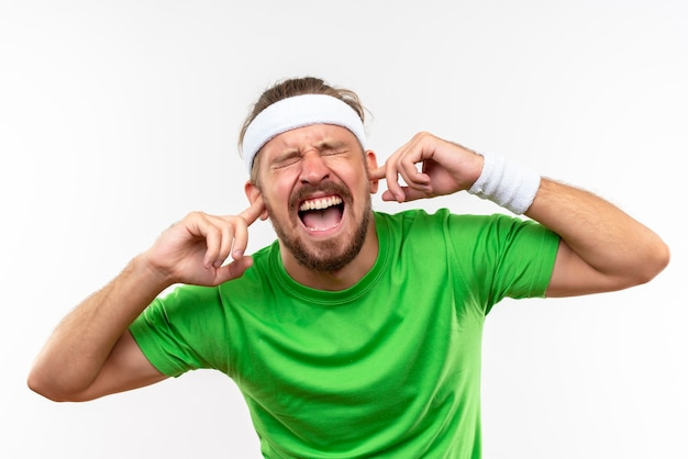 Angry young handsome sporty man wearing headband and wristbands putting fingers in ears with closed eyes isolated on white wall
