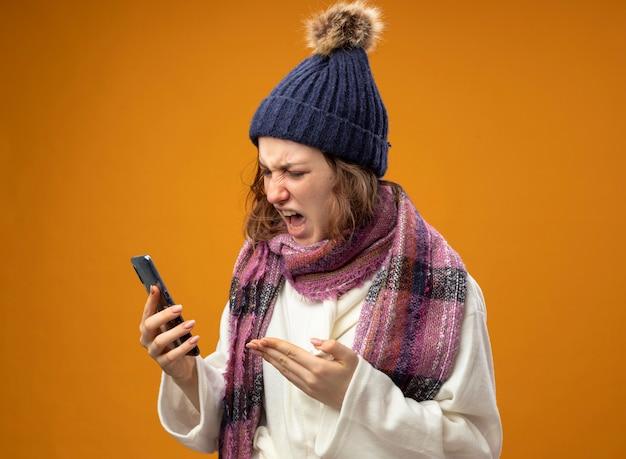 白いローブと冬の帽子を身に着けている怒っている若い病気の女の子がスカーフを保持し、オレンジ色の壁に分離された電話で手でポイント