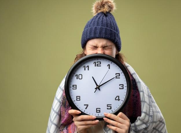 Arrabbiato giovane ragazza malata che indossa una veste bianca e cappello invernale con sciarpa viso coperto con orologio da parete avvolto in un plaid isolato su verde oliva