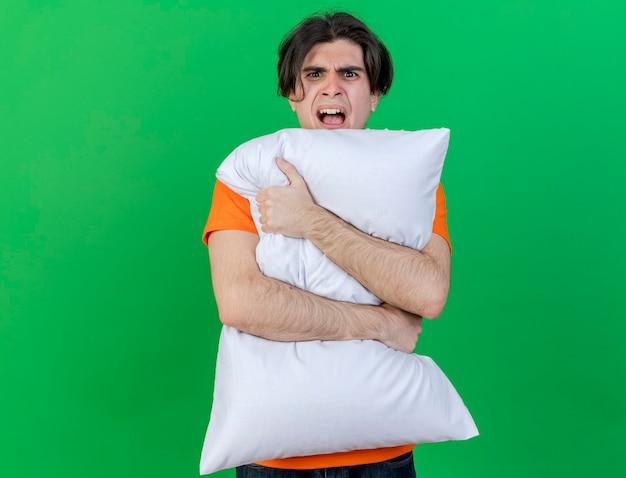 緑の背景に分離された怒っている若い病気の人抱き枕