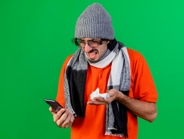 Angry young ill man wearing glasses winter hat and scarf holding and looking at mobile phone and holding napkin isolated on green wall with copy space