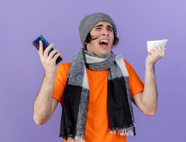 紫色の背景で隔離のナプキンと電話を保持しているスカーフと冬の帽子をかぶって怒っている若い病気の男