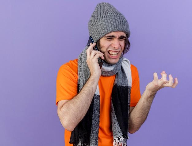 Arrabbiato giovane uomo malato che indossa il cappello invernale con sciarpa parla al telefono isolato su sfondo viola