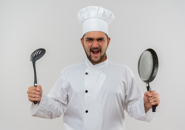 Angry young male cook in chef uniform holding slotted spoon and frying pan isolated on white wall