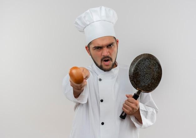 フライパンを持ち、コピー スペースで白い壁に分離されたスプーンを伸ばすシェフの制服を着た怒っている若い男性料理人