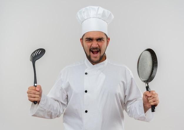 スロット スプーンと白い壁に分離されたフライパンを保持しているシェフの制服を着た怒っている若い男性料理人