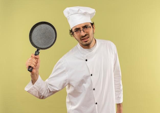 シェフの制服とフライパンを上げる眼鏡を身に着けている怒っている若い男性料理人