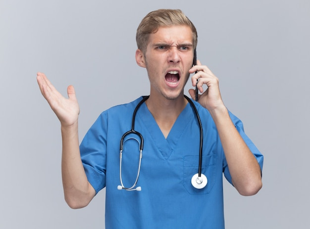 聴診器で医者の制服を着て怒っている若い男性医師は白い壁に隔離された手を広げて電話で話します