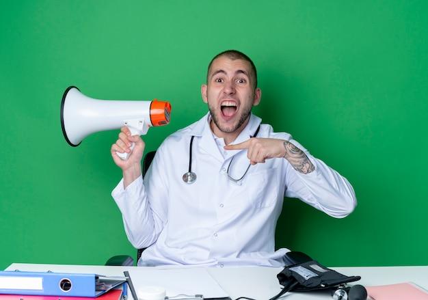 의료 가운과 청진기를 착용하고 스피커를 잡고 그것을 가리키는 작업 도구로 책상에 앉아 녹색에 고립 된 큰 소리로 외치는 화가 젊은 남성 의사