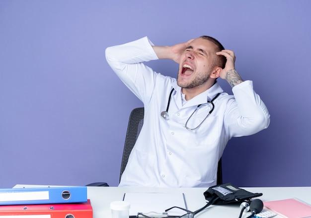 医療ローブと聴診器を身に着けている怒っている若い男性医師は、紫色で隔離された目を閉じて頭に手を置く作業ツールで机に座っています