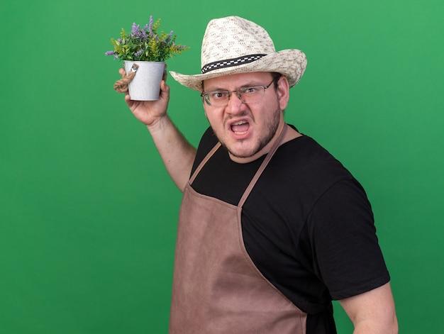 Giovane giardiniere maschio arrabbiato che indossa il cappello di giardinaggio che tiene fiore in vaso di fiori isolato sulla parete verde con lo spazio della copia