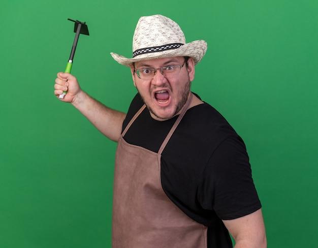 緑の壁に分離されたくわ熊手を保持しているガーデニング帽子をかぶって怒っている若い男性の庭師
