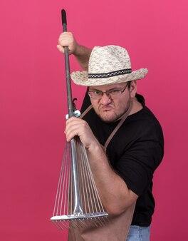 분홍색 벽에 고립 된 잎 갈퀴를 들고 뜰을 만드는 모자를 쓰고 화가 젊은 남성 정원사
