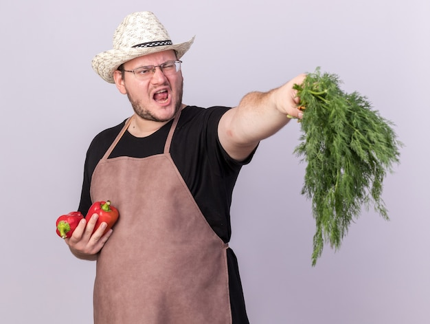 Angry young male gardener wearing gardening hat holding out peppers with dill  isolated on white wall