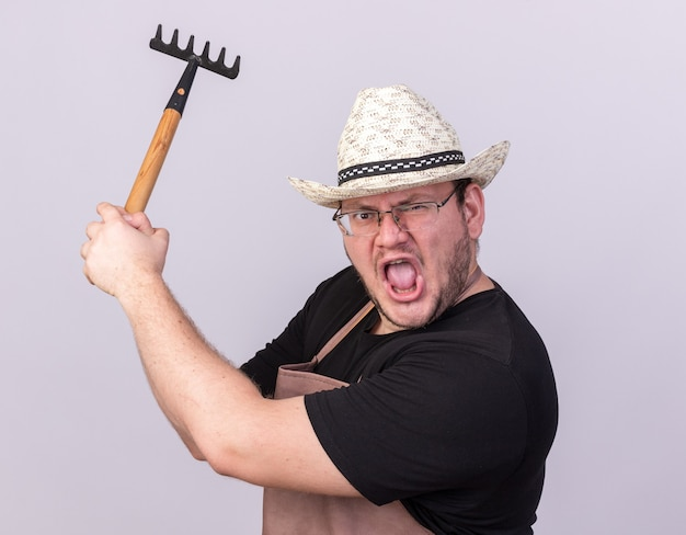 Angry young male gardener wearing gardening hat holding rake isolated on white wall