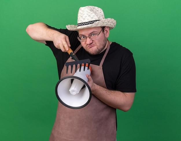 Сердитый молодой мужчина-садовник в садовой шляпе царапает громкоговоритель с граблями, изолированными на зеленой стене