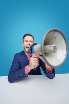 Angry young male manager or boss shouting in megaphone while making announcement or warning