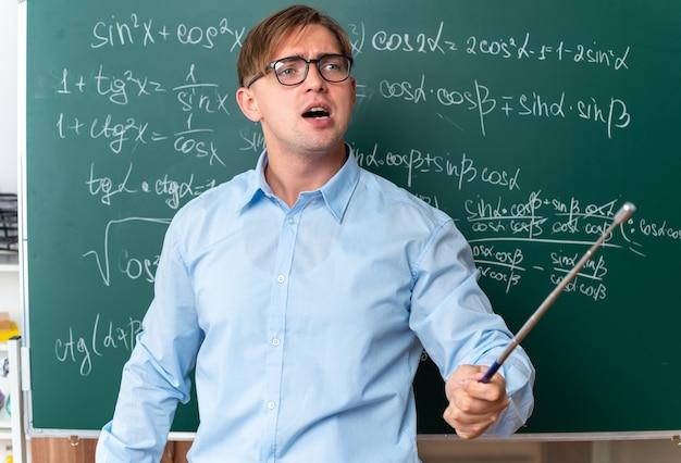 Arrabbiato giovane insegnante maschio con gli occhiali con puntatore che spiega la lezione in piedi vicino alla lavagna con formule matematiche in classe