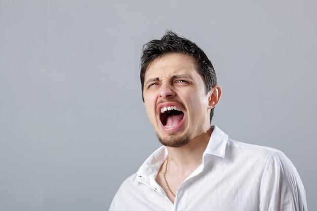 灰色の背景で叫んで白いシャツを着たブルネットの怒っている若い男。