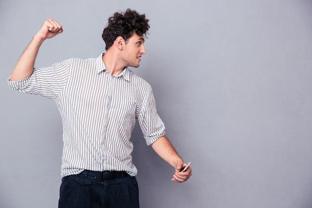 彼の拳を握りしめている怒っている若い男