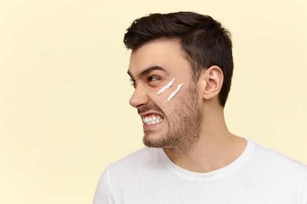 Giovane arrabbiato che fa routine mattutina con crema lozione sul viso