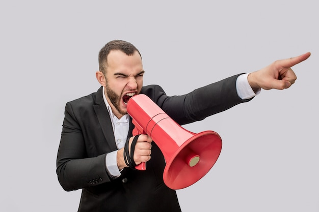 Angry young man hold red megaphone in hand nad screma into it. he points forward. guy is mad.