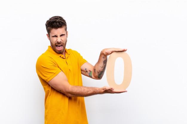 Злой молодой человек держит номер 0