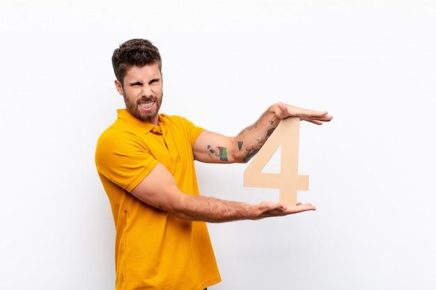 Злой молодой человек держит номер 4