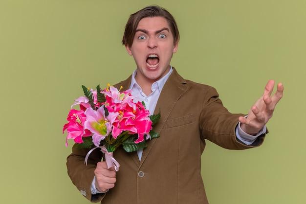 緑の壁の上に立って腕を上げた国際女性の日を積極的な表情で叫んで正面を見て花の花束を保持している怒っている若い男