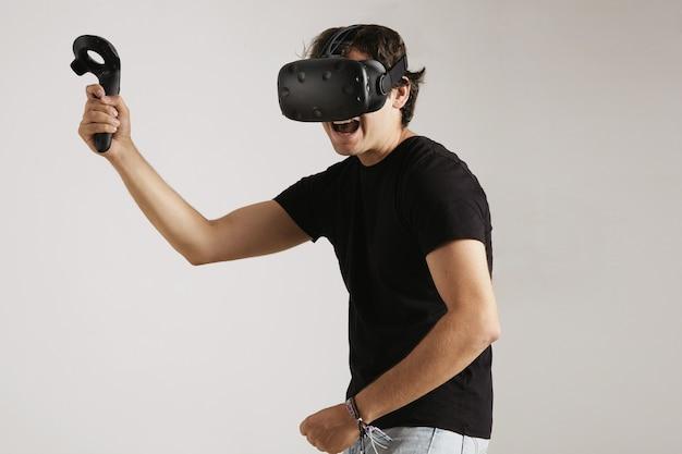 Vr 헤드셋과 검은 면화 티셔츠에 화난 젊은이가 격투 게임을합니다.