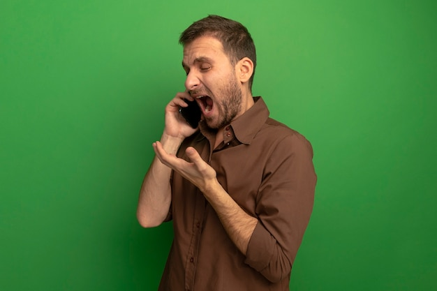 프로필보기에 서있는 성 난 젊은이 녹색 벽에 고립 된 빈 손을 보여주는 전화 통화