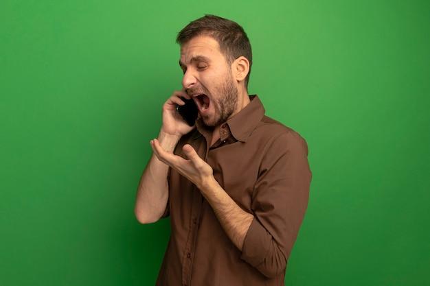 Giovane arrabbiato che sta nella vista di profilo che parla sul telefono che mostra la mano vuota isolata sulla parete verde