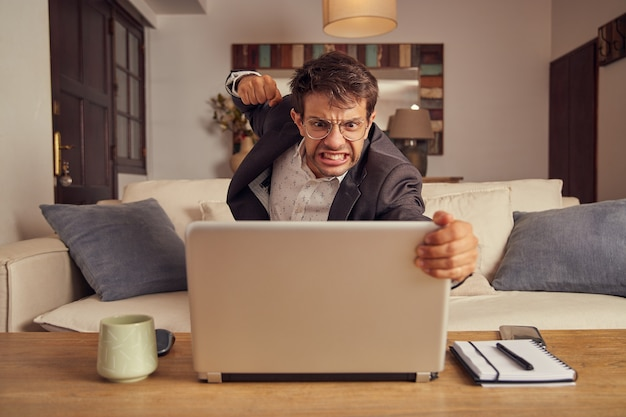 Angry young man in suit hitting his laptop computer with his fist. sitting on the sofa at home. work from home.