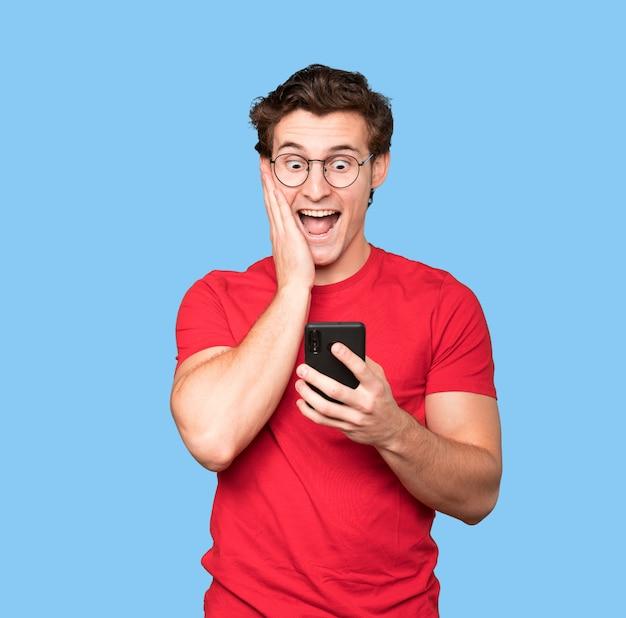 Сердитый молодой человек с помощью мобильного телефона