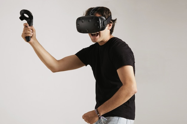 Angry young man in vr headset and black cotton t-shirt playing a fighting game