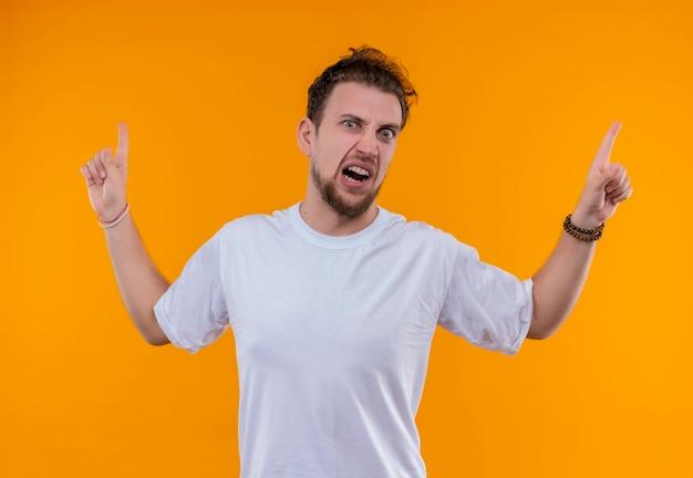 白いtシャツを着て怒っている若い男は、孤立したオレンジ色の壁を指しています