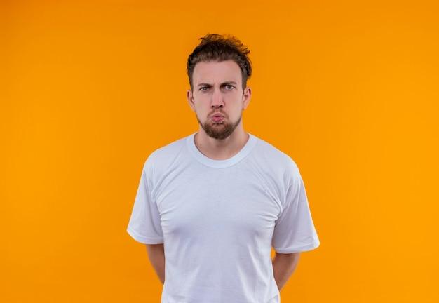 Il giovane arrabbiato che indossa la maglietta bianca ha messo la sua mano sulla parte posteriore sulla parete arancione isolata