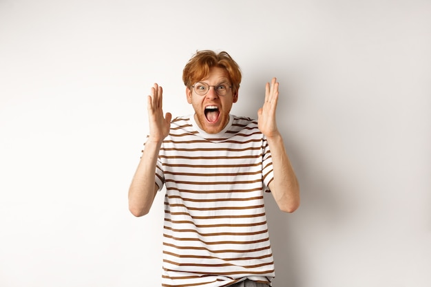 Angry young man with red hair shouting at camera, screaming and looking outraged, shaking hands, standing over white background.