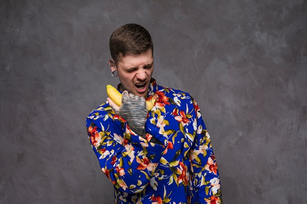 An angry young man with tattooed on his hand shouting on banana phone against gray wall