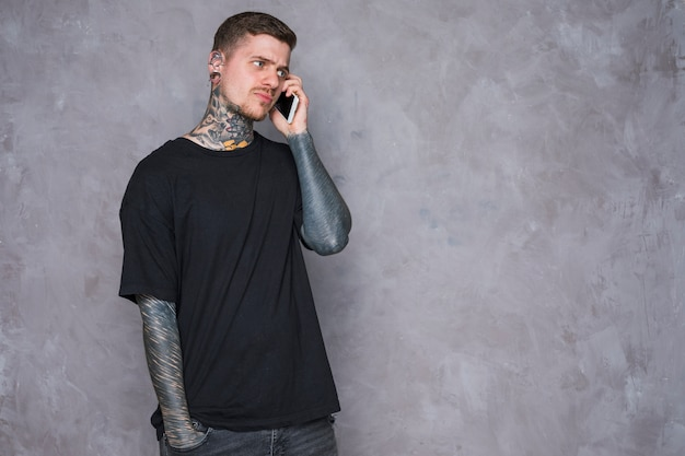 An angry young man with tattooed on his hand talking on mobile phone against grey wall