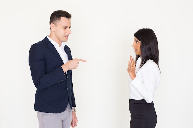Angry young north american businessman blaming female indian colleague on fault.