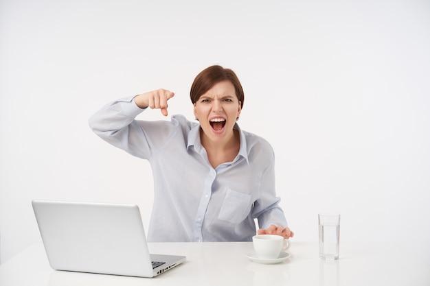 Arrabbiato giovane donna dai capelli castani con taglio di capelli corto alla moda che grida ferocemente con la bocca larga aperta e che punta con il dito indice, isolato su bianco