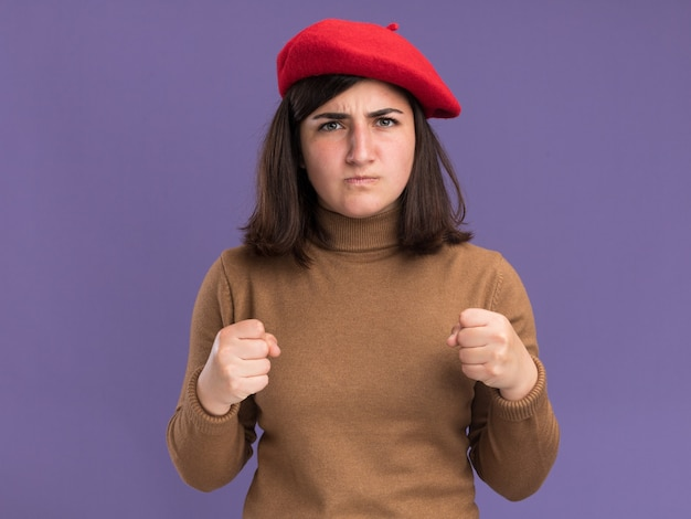 Angry young pretty caucasian girl with beret hat keeping fists isolated on purple wall with copy space