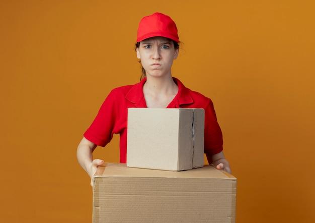 Ragazza di consegna graziosa giovane arrabbiata in uniforme rossa e cappuccio che tiene le scatole di cartone che guarda l'obbiettivo isolato su fondo arancio con lo spazio della copia