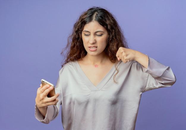 Ragazza graziosa giovane arrabbiata che tiene e che esamina telefono e che alza il pugno